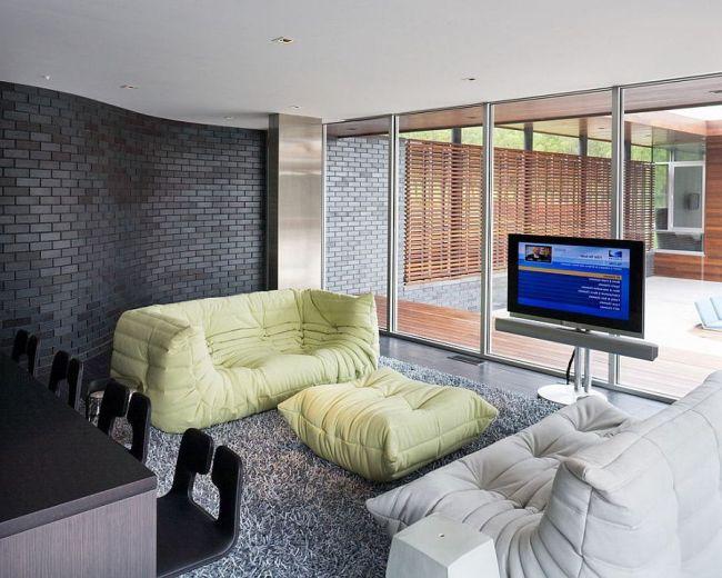 Гостиная с преобладанием серых оттенков и волнообразной кирпичной стеной