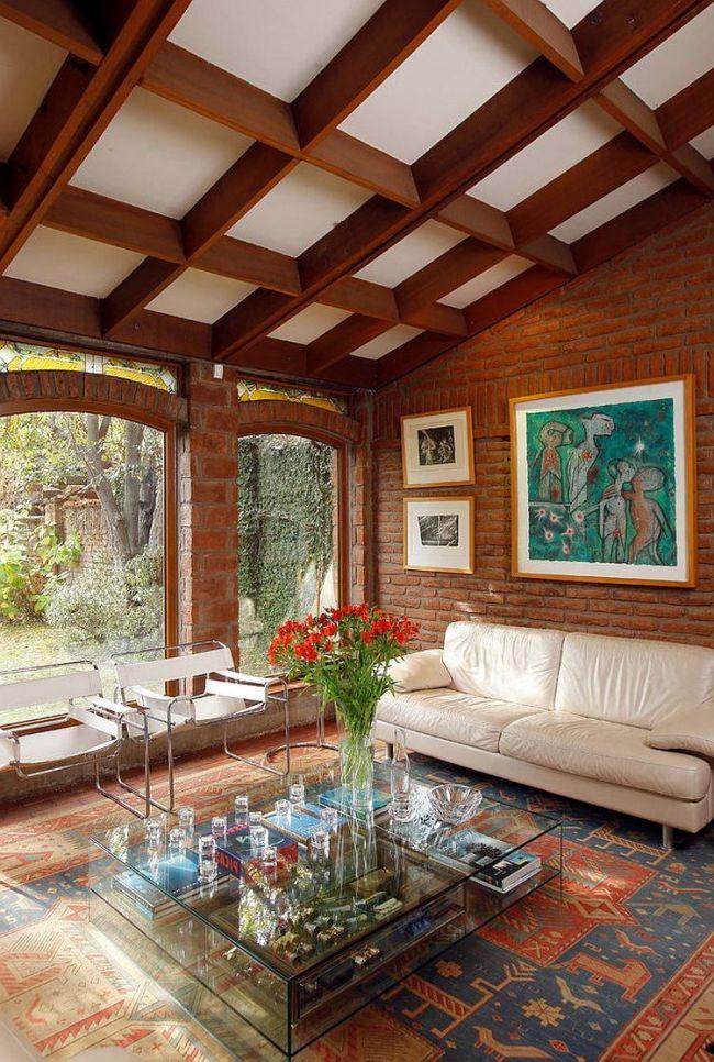 Современная гостиная с кирпичными стенами, большими окнами и пересекающимися потолочными балками