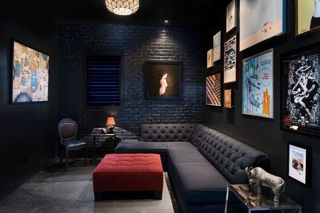 Черная гостиная с кирпичной стеной и множеством постеров
