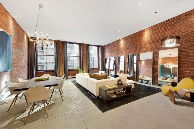 Большая светлая гостиная с кирпичной стеной и зеркалами