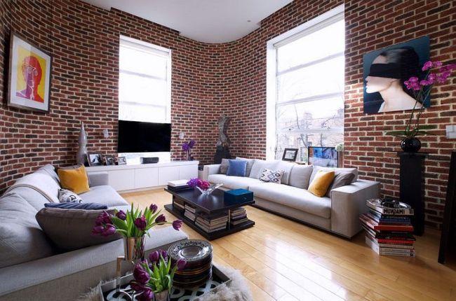 Гостиная с высоким потолком и изогнутой кирпичной стеной