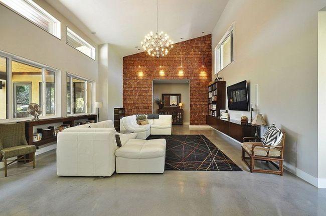 Просторная белая гостиная с геометричной стеной из красного кирпича